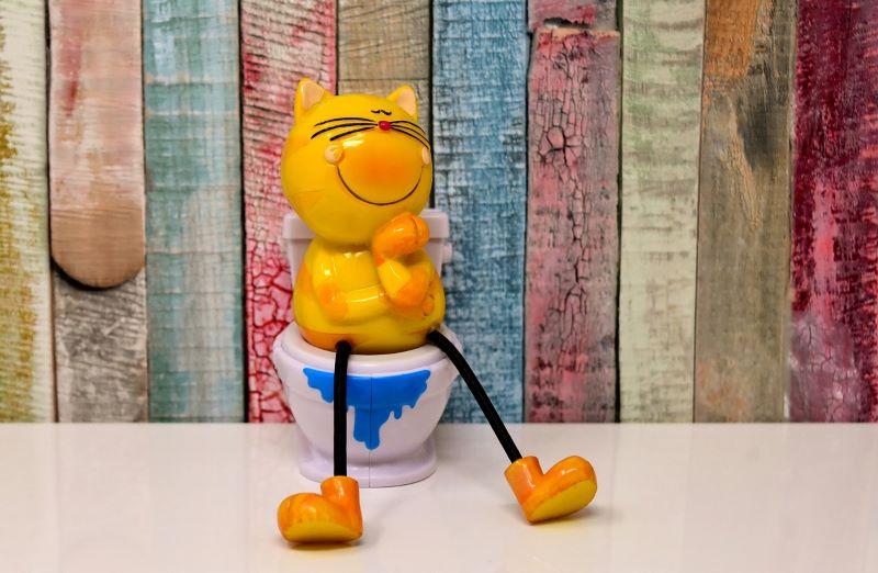 Фигурка желтого кота с довольной мордочкой сидит на унитазе